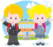 Schoolchildren before a school. Schoolgirl and schoolboy standing in front of their school and waving hands in greeting Royalty Free Stock Photo