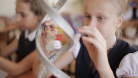Schoolchildren in school uniform are studying the layout of dna sitting in the classroom. The concept of school. High school students in school uniform study the stock footage