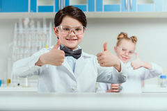 Schoolchildren showing thumbs up in chemical lab. Scientists kids team concept Royalty Free Stock Photo