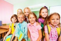 Schoolchildren sitting close near desk and smile Royalty Free Stock Photo