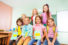 Schoolchildren sitting close together near desk Royalty Free Stock Image