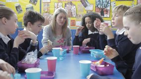 Schoolchildren Sitting Eating Packed Lunch With Teacher stock video