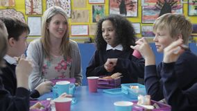 Schoolchildren Sitting Eating Packed Lunch With Teacher stock video footage