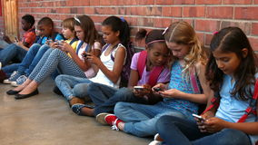 Schoolchildren sitting outside using phones stock video