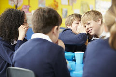 Schoolchildren Sitting At Table Eating Packed Lunch Stock Image