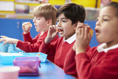 Schoolchildren Sitting At Table Eating Packed Lunch Royalty Free Stock Photography