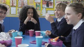 Schoolchildren Sitting At Table Eating Packed Lunch stock video