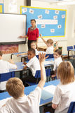 Schoolchildren Studying In Classroom With Teacher stock image