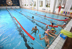 Schoolchildren swim in the covered sports public swimming pool. Royalty Free Stock Image