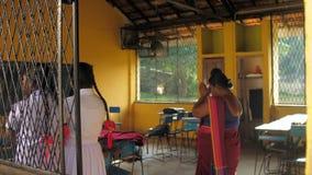 Schoolchildren and teacher pray in classroom with board. Colombo/Sri Lanka - April 05 2019: Schoolchildren in uniforms and teacher in dress pray in classroom stock video footage