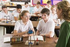 Schoolchildren and teacher in science class stock photography