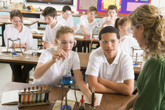 Schoolchildren and teacher in science class stock photos