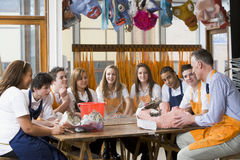 Schoolchildren and teacher sitting around a table Royalty Free Stock Photos