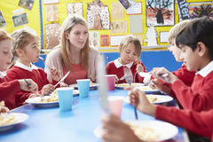 Schoolchildren With Teacher Sitting At Table Eating Lunch Royalty Free Stock Photo