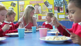 Schoolchildren With Teacher Sitting At Table Eating Lunch stock video