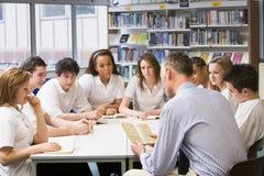 Schoolchildren and teacher studying Royalty Free Stock Photos