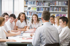 Schoolchildren and teacher studying Royalty Free Stock Photography