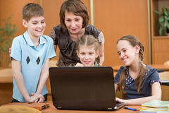Schoolchildren and teacher using notebook at lesson Royalty Free Stock Photo