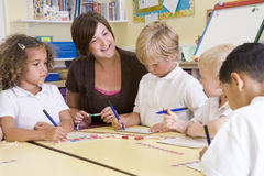 Schoolchildren and their teacher in a class Royalty Free Stock Photo