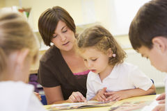 Schoolchildren and their teacher reading in class Royalty Free Stock Photos