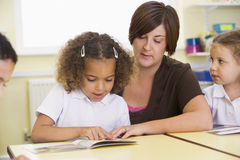 Schoolchildren and their teacher reading in class Stock Photography