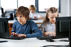 Schoolchildren Using Desktop Pc In Computer Lab. Cute little schoolchildren using desktop PC at desk in computer lab Royalty Free Stock Photography