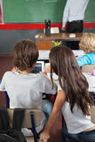 Schoolchildren Using Digital Tablet In Classroom. Rear view of schoolchildren using digital tablet at desk in classroom Royalty Free Stock Photography