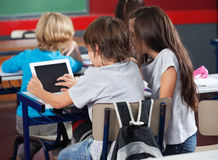 Schoolchildren Using Digital Tablet In Classroom. Rear view of little schoolchildren using digital tablet at desk in classroom Stock Images