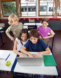 Schoolchildren Using Laptop At Desk In Classroom Stock Image