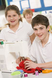 Schoolchildren using a sewing machine Royalty Free Stock Images