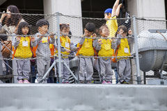 Schoolchildren visit the War Memorial of Korea. Korean children on a visit to the War Memorial of Korea, standing behind a wire fence, wearing high visibility Stock Photo