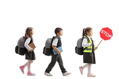 Schoolchildren walking, a schoolgirl holding a stop sign. Full length profile shot of schoolchildren walking and a schoolgirl holding a stop sign isolated on royalty free stock photos