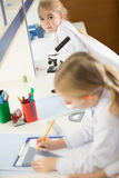 Schoolchildren in white lab coats studying together and making notes. In laboratory stock image