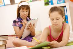Schoolchildren writing into booklet Royalty Free Stock Photo
