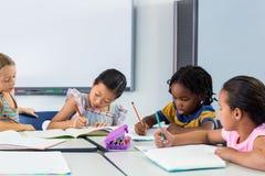 Schoolchildren writing on books Stock Photography