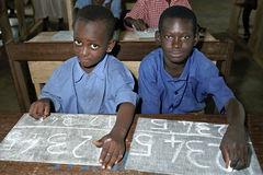 Schoolchildren writing with chalk on a slate royalty free stock image