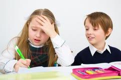 Schoolchildren writing at school. Little schoolchildren writing at school in workbook Royalty Free Stock Image
