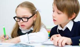 Schoolchildren writing at school. Little schoolchildren writing at school in workbook Royalty Free Stock Photography