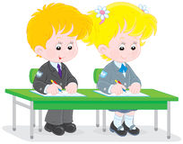 Schoolchildren writing. Schoolgirl and schoolboy write in their exercise books at a lesson Stock Photography
