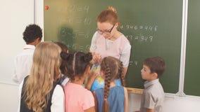 Schoolchilds que mira el globo con el profesor la lección de la geografía metrajes