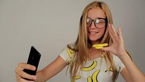 Schoolerflickan roterar spinnaren för selfie stock video