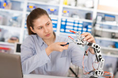Schoolgirl adjusts robot arm model Royalty Free Stock Images