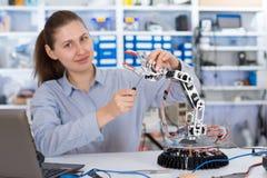 Schoolgirl adjusts the robot arm model. Girl in  robotics laboratory Royalty Free Stock Photography