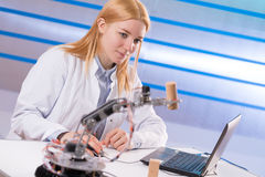 Schoolgirl adjusts the robot arm model Royalty Free Stock Image