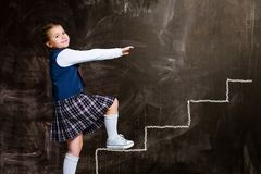 Schoolgirl against chalkboard, with drawn steps royalty free stock images