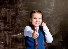 Schoolgirl against chalkboard, with her thumb up royalty free stock images
