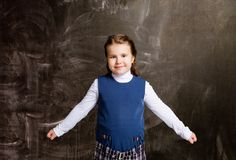 Schoolgirl against chalkboard, with spread arms stock images