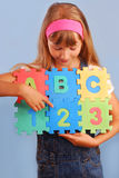 Schoolgirl with alphabet puzzle Royalty Free Stock Photography
