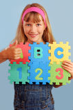 Schoolgirl with alphabet puzzle Stock Photo