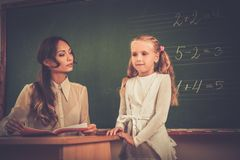 Schoolgirl answering near blackboard Royalty Free Stock Image